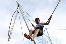 Happy Kid Jumping On Bungee Tr...