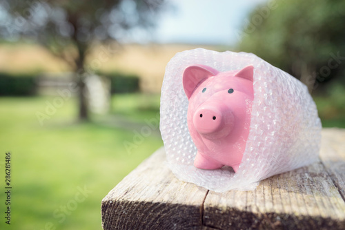 Valokuvatapetti Piggy bank wrapped in bubble wrap, protecting your money