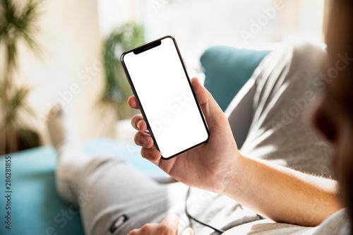 Foto  Man using smartphone blank screen frameless modern design while lying on the sof