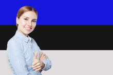 Estonia. Happy Cute Girl Showing Thumb Up And Smiling On Estonia