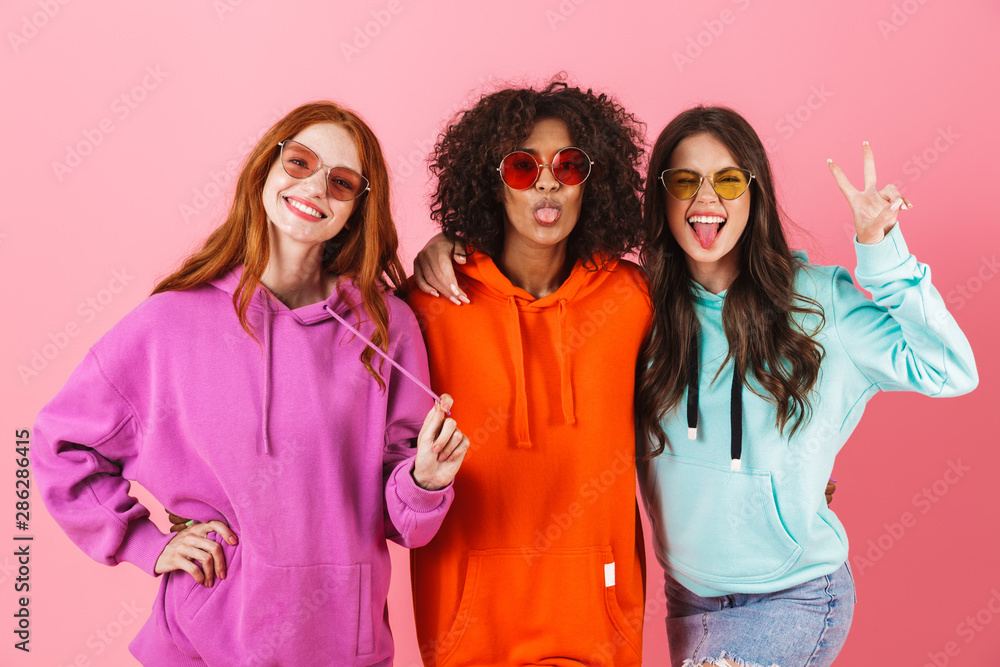 Fototapety, obrazy: Three happy young girls wearing colorful hoodies standing