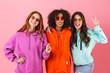 Leinwandbild Motiv Three happy young girls wearing colorful hoodies standing