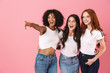 Cheerful cute multi-ethnic girls friends posing isolated over pink wall background pointing.