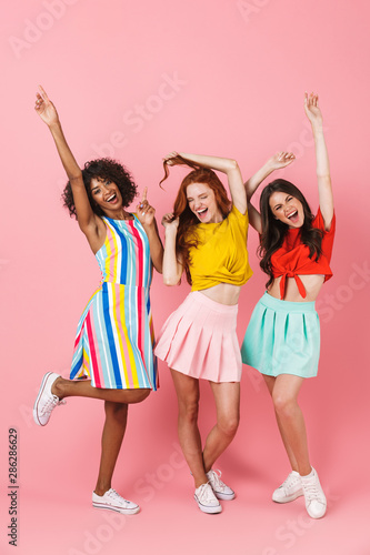 Happy emotional young three multiethnic girls friends posing isolated over pink wall background dancing.