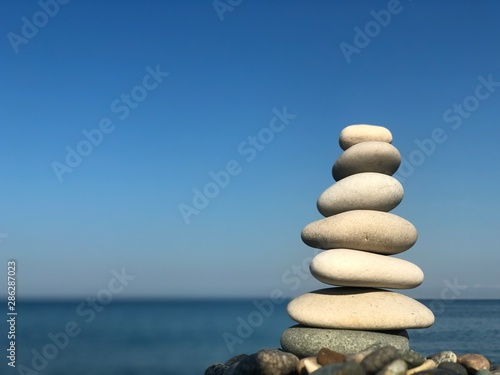 Photo sur Toile Zen pierres a sable Marine theme: stones on the shore. The stones are stacked in a pyramid against the background of the sea. Pyramid of small stones on the beach. The concept of harmony of balance and meditation.