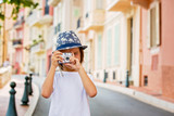 Fototapeta Uliczki - Children taking pictures on a narrow street with houses in Monaco-Ville, Monaco on a cloudy day