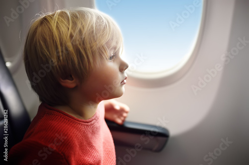 Fotografía  Charming kid traveling by an airplane