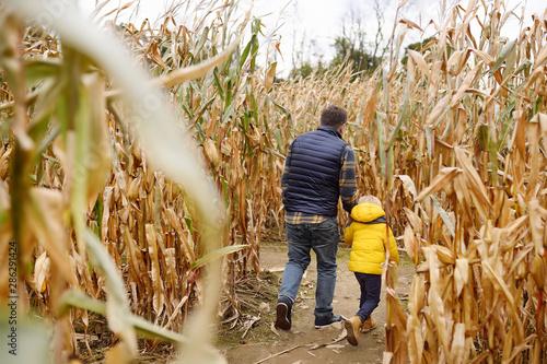 Fényképezés Little boy and his father having fun on pumpkin fair at autumn