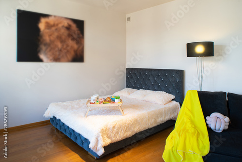Slika na platnu Kingsize bed in studio apartment. Laid tray.