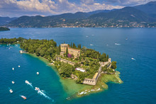 Unique View Of The Island Of Garda. In The Background Is The Alps. Resort Place On Lake Garda North Of Italy. Aerial Photography.
