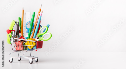 Fotografía Shopping cart with office stationery isolated on white