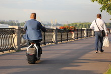 A Young Man Fast Rides On Electric Scooter With Big Wheels Overtaking Of Pedestrian In The City On An Asphalt Road Embankment On A Summer Day - Personal City Transport