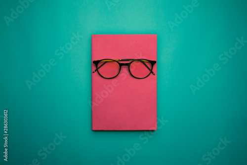 Fotografie, Obraz  Glasses, book and stationery placed on blue background, Back to school concept,