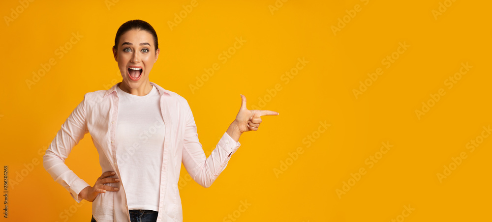 Fototapeta Surprised Lady Pointing Finger At Free Space On Yellow Background