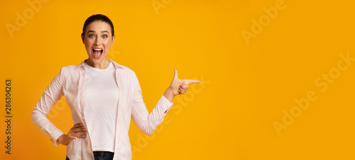 Surprised Lady Pointing Finger At Free Space On Yellow Background