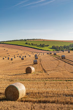 A Summer Landscape In The South Downs In Sussex, With Hay Bales In A Newly Harvested Field