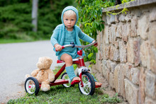 Adorable Toddler Boy With Knitted Outfit, Riding Tricycle On A Quiet Village Street