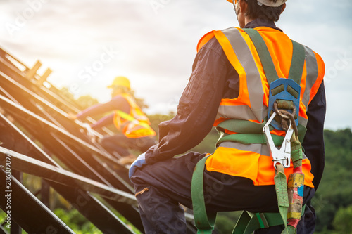 [safety body construction] Working at height equipment. Fall arrestor device for worker with hooks for safety body harness on selective focus. Worker as in construction background.
