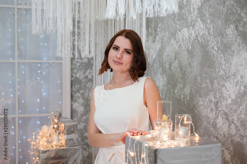 A beautiful happy woman in a white evening dress is standing near the Christmas garland and decorations. New Year celebration