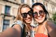 Happy young women in sunglasses taking selfie