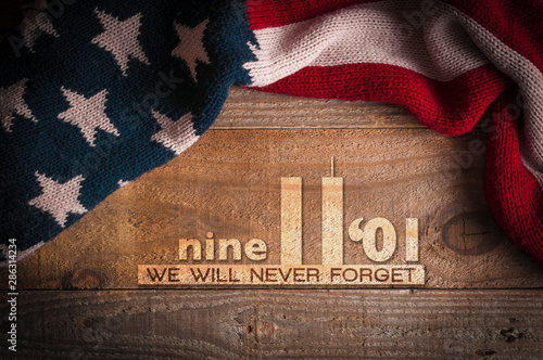 Tela  A scarf with the colors of the American flag on a wooden table and an inscription in memory of September 11th