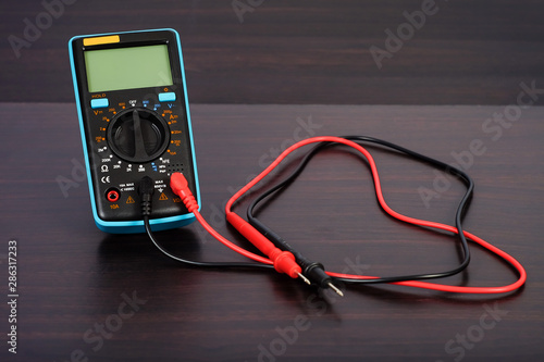 Digital multimeter with probes on a white background. Wallpaper Mural