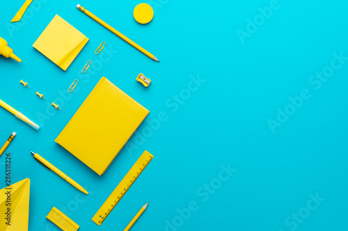 Fotomural Top view photo of yellow stationery over turquoise blue background with copy space