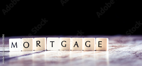 Photo Mortgage word made of tiles on dark wooden background