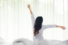 Asian Women Waking Up Stretching In Bed Room At Home, Early Morning Time And Sunny Day. Lifestyle Concept