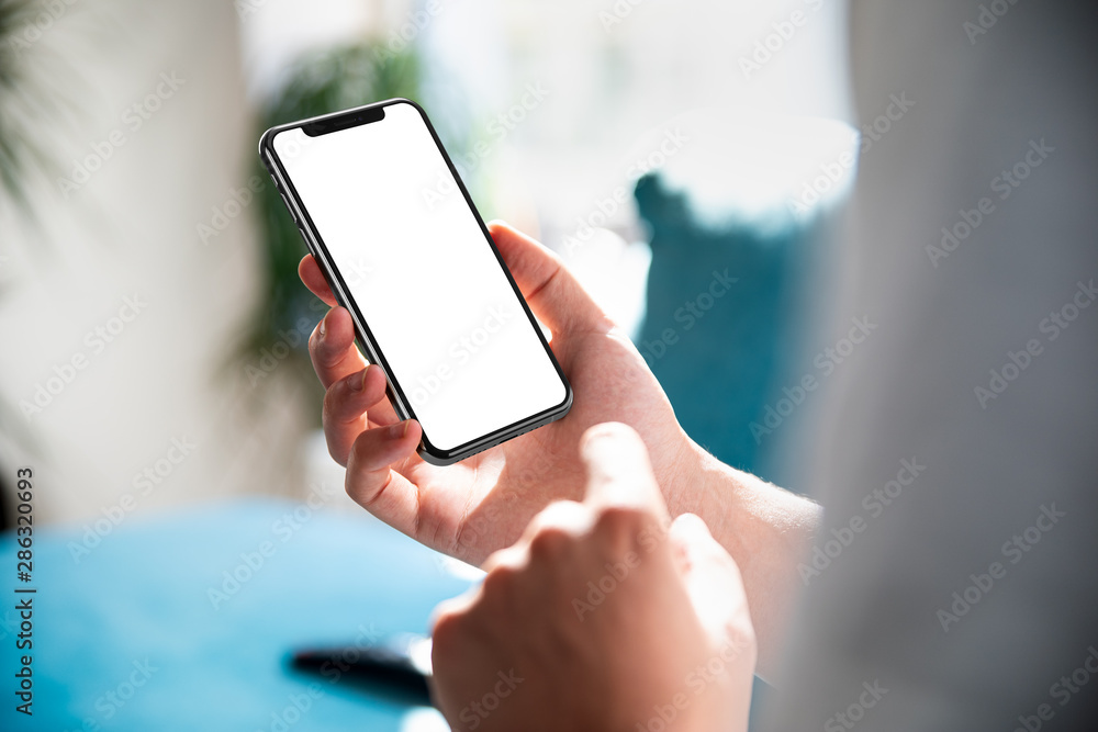 Fototapeta Man using smartphone blank screen frameless modern design while lying on the sofa in home interior