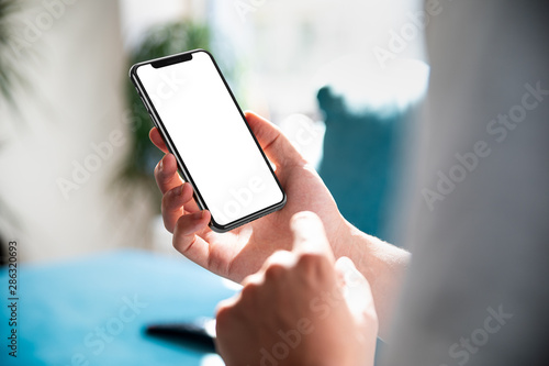 Man using smartphone blank screen frameless modern design while lying on the sofa in home interior