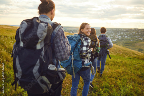 Obraz Group of friends trekking with backpacks walking in the forest . - fototapety do salonu