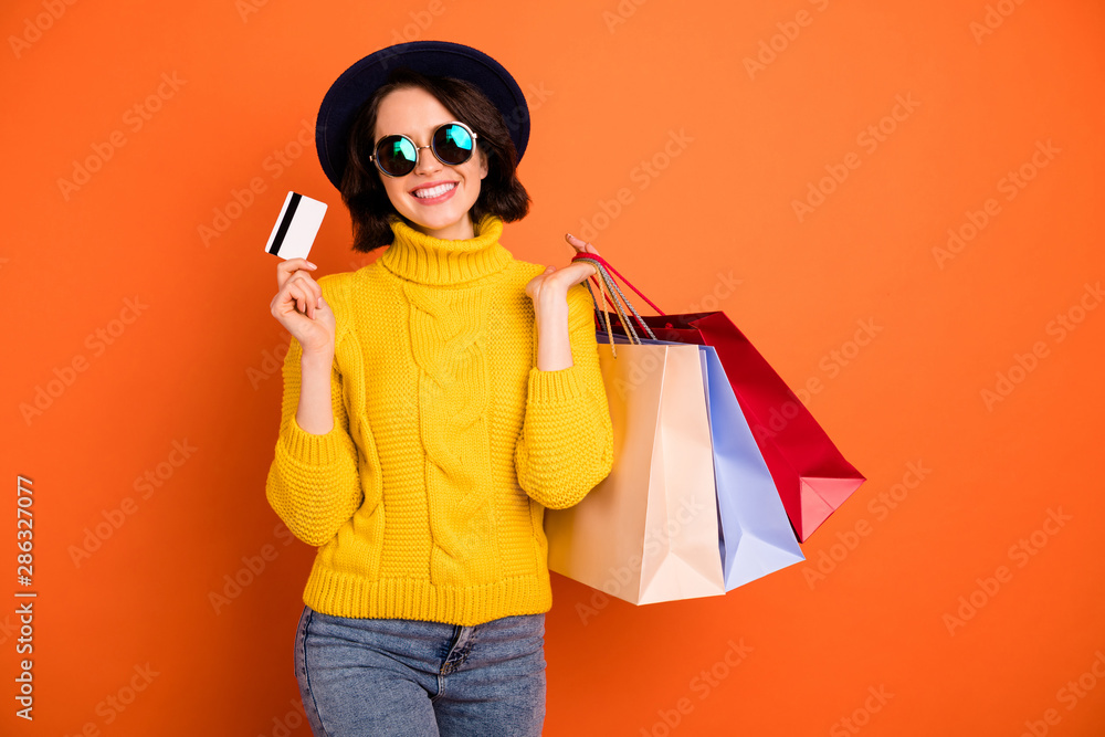 Fototapeta Photo of wealthy trendy cheerful nice girl having found discounts and sales at shopping mall and bought lots of packages while isolated with orange background