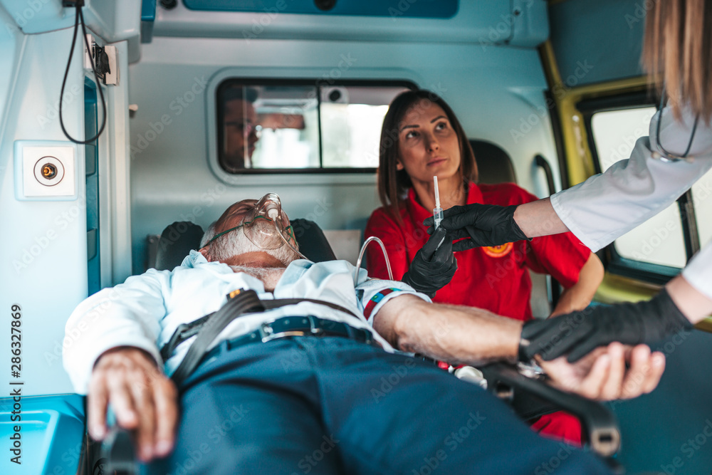 Fototapety, obrazy: Emergency medical service at work. Paramedic giving first aid to senior man with serious heart attack inside of ambulance car. Help on the road. Drivers assistance concept.