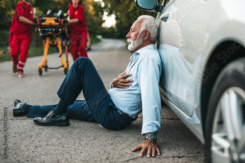 Fotografia Elegant senior man with heart attack symptoms sitting on the road emergency medical service workers trying to help him