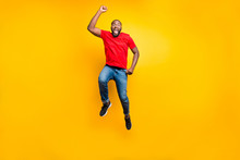 Full Length Body Size Photo Of Jumping Man Wearing Red T-shirt Jeans Denim Rejoicing With His Victory At Something While Isolated With Yellow Background
