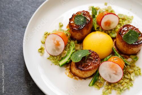 Fotografia King oyster mushroom scallops, confit yolk and wasabi peas crumbs