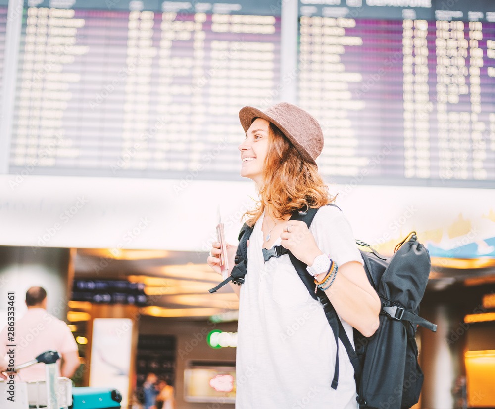 Fototapety, obrazy: Happy young girl traveler at the airport with a backpack on the background of a departures board