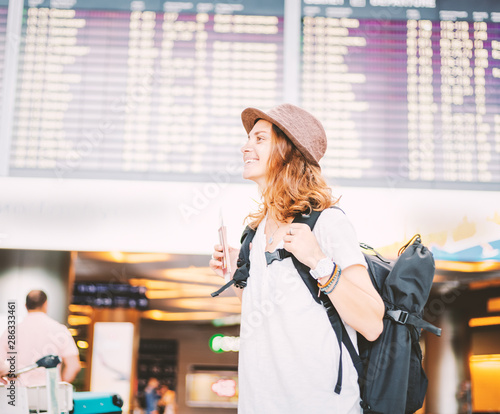 Happy young girl traveler at the airport with a backpack on the background of a departures board - 286333461