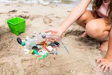 Child Sorting Through Plastic Litter On Beach