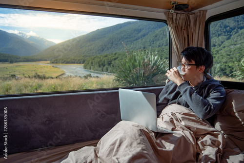 Obraz na plátne Young Asian man drinking milk while working with laptop computer on the bed in camper van with mountain scenic view through the window