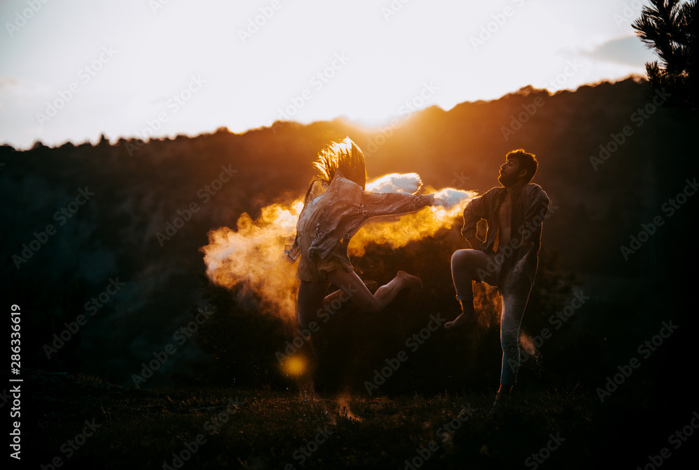 Fototapeta Modern style dancers posing on mountain against blue sky