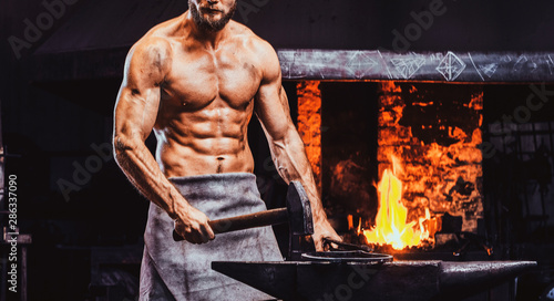 Fotografia, Obraz Powerful bearded blacksmith with naked torso and protective apron is standing near working stove with hammer in his hand