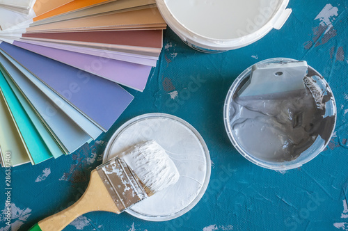Fototapety, obrazy: Choose a paint color for the walls. Spatula for painting and wall putty and background in a tray next to a bucket of putty.. Create a background