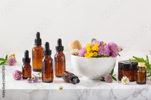 Fotografía  medical flowers herbs in mortar essential oils in bottles