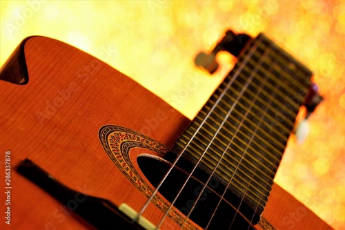 The guitar is a stringed plucked musical instrument, with bokeh lights in the background Canvas Print