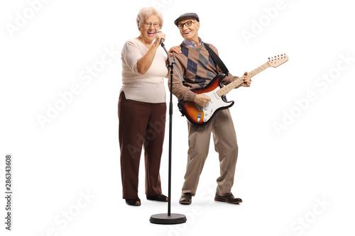 Fototapeta Elderly woman singing on a microphone and an elderly gentleman playing a guitar