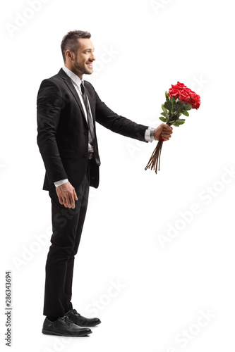 Fotografía Young elegant man smiling and giving a bunch of red roses