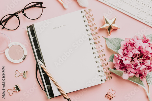 Photo Female workspace with laptop, pink hydrangea, golden accessories, pink diary on pink background