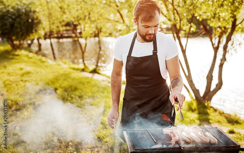 Fototapeta Chef smoking sausages on grill obraz